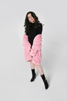 Полнометражное изображение великолепной женской модели с длинными вьющимися волосами брюнетки в черном боди и фут-пальто, изолированном белом фоне. вертикальный вид.