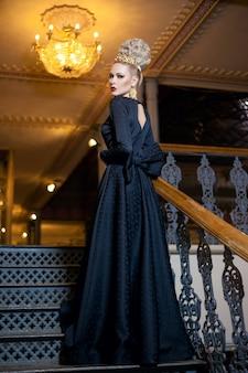 エレガントな髪型の素晴らしい王冠とイヤリングを備えた、長い黒のドレスを着た偉大な若いブロンドの女性の全身像。