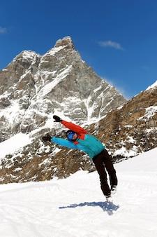 Изображение в полный рост лыжника, прыгающего в снаряжении, на высокой горе
