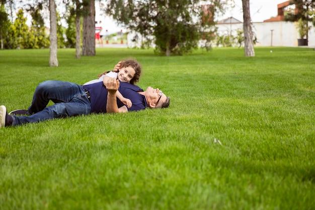 晴れた日に公園で祖父を抱きしめる姪の全身像は、緑の芝生の上に横たわっています。