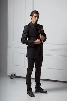 Полнометражное изображение стильного уверенно молодого человека в черном костюме, смотрящего в камеру, на сером фоне. вертикальный вид.