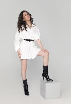 Полнометражное изображение молодой брюнетки кудрявой женщины с прической и косметикой, в длинной белой рубашке и высоком каблуке, позирующем в студии. вертикальный вид.