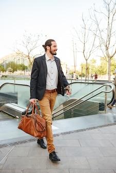 スタイリッシュなフォーマルな服装で大人のビジネスマンの完全な長さの画像、地下鉄から立ち上がって、革の男性のバッグと新聞を手に歩いて