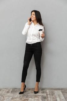 立っていると灰色の背景に分離されたテイクアウトコーヒーの紙コップを手に携帯電話を持っているフォーマルな服装で魅力的なビジネス女性の完全な長さの画像