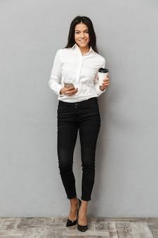 立っていると灰色の背景に分離された持ち帰り用のコーヒーの紙コップを手に携帯電話を手に保持しているフォーマルな服装で魅力的なビジネス女性の完全な長さの画像