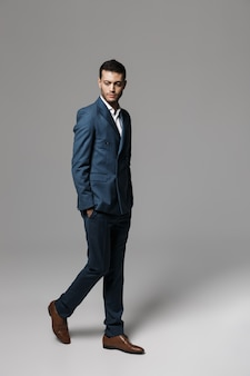 Изображение делового арабского мужчины 30-х в полный рост в официальном костюме, гуляющего, изолированное над серой стеной