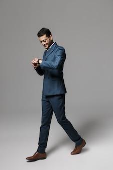 Изображение в полный рост веселого арабского мужчины 30-х годов в официальном костюме, гуляющего, изолированное над серой стеной