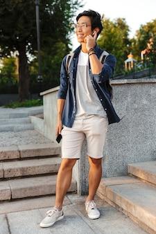 スマートフォンで話し、屋外を見て眼鏡をかけた陽気なアジアの男子学生の完全な長さの画像