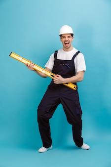Полное изображение веселого мужчины-строителя в защитном шлеме, развлекающегося с инструментом уровня, глядя на
