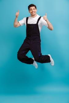Изображение в полный рост веселого мужчины-строителя, дергающего за синюю стену и показывающего большие пальцы руки вверх