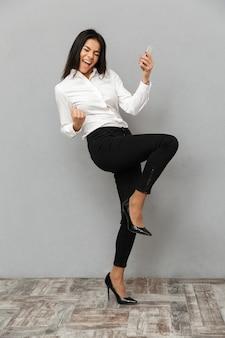 灰色の背景に分離された携帯電話で手に成功したオフィス摩耗喜びと握りこぶしで拳を喜んでビジネスライクな女性の完全な長さの画像