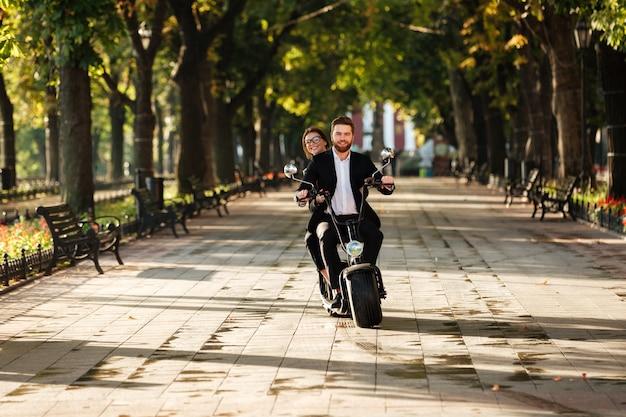 モダンなバイクに乗るエレガントなカップルの全長画像