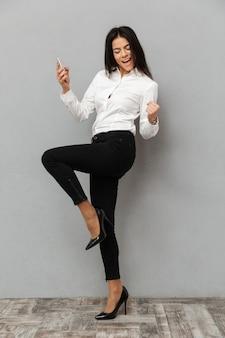正式な摩耗で興奮しているビジネス女性の完全な長さのイメージを着用して喜びや握りこぶしで成功または灰色の背景に分離された携帯電話を手にして喜び