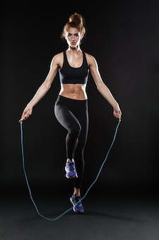 Полная длина образ фитнес женщина прыгает со скакалкой