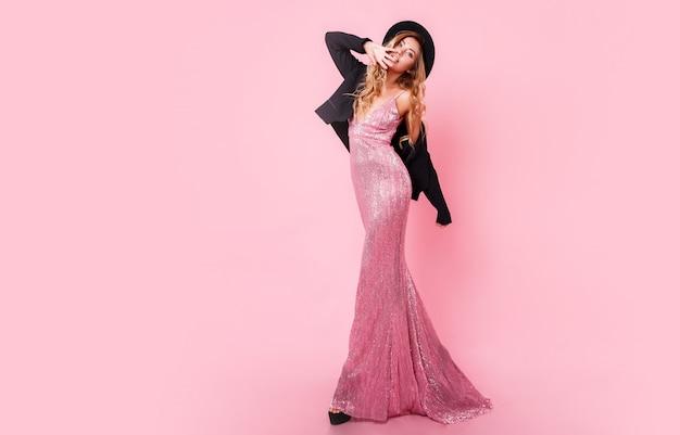 スパンコールマキシドレスとピンクの壁でポーズスタイリッシュな黒い帽子で優雅なセクシーなブロンドの女性の完全な長さの画像。素晴らしい姿。ヒールの高さ。ショッピング。おしゃれな表情。