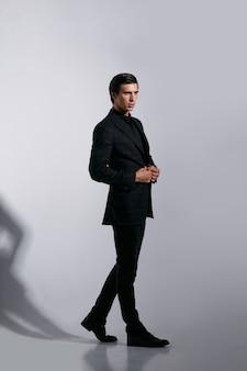 Полное изображение красивой мужской модели в черном стильном костюме, изолированном на белом фоне.