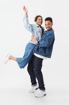 灰色の壁の上に彼のガールフレンドを抱きかかえた男が一緒に楽しんでいるデニムシャツで幸せなアフリカカップルの完全な長さの画像