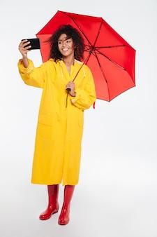 レインコートの傘の下に隠れて、白い背景の上の彼女のスマートフォンでselfieを作る幸せなアフリカ女性の完全な長さの画像