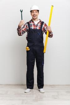 レベルツールとレンチを保持している保護用のヘルメットで幸せな男性ビルダーの完全な長さの画像