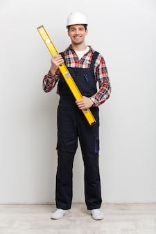 Полное изображение счастливого мужчины-строителя в защитном шлеме, держащего инструмент уровня над серой стеной