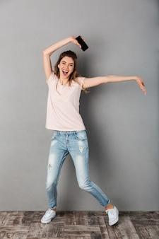 Полнометражное изображение счастливой кричащей женщины в футболке, слушая музыку со смартфона и весело проводя время над серым