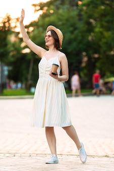 Полнометражное изображение счастливой женщины в платье, соломенной шляпе и солнцезащитных очках, машущей и глядя в сторону на открытом воздухе
