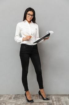 비즈니스 다운 복장과 클립 보드를 들고 회색 배경 위에 절연 서류에 메모를 작성하는 안경을 착용하는 사랑스러운 여자의 전체 길이 이미지