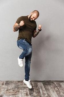 Полнометражное изображение мускулистого счастливого человека с бородой и усами, радующегося и сжимающего кулаки, изолированного над серой стеной