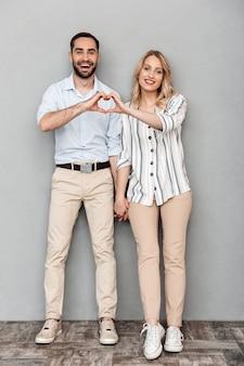 笑顔と指を分離してハートの形を示すカジュアルな服を着た素敵なカップルの完全な長さの画像
