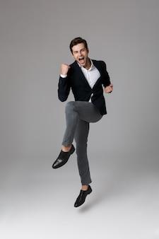 Полное изображение позитивного бизнесмена 30-х годов в строгом костюме, кричащего и сжимающего кулаки, изолированного над серой стеной