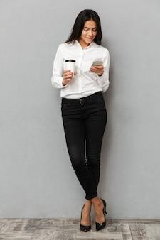 立っていると灰色の背景に分離された手にテイクアウトのコーヒーを携帯電話を使用してフォーマルな服装でかなりビジネス女性の完全な長さの画像