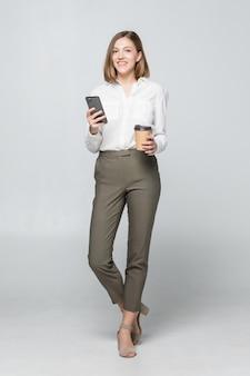 Полное изображение красивой деловой женщины в формальной одежде, стоящей и использующей мобильный телефон с кофе на вынос в руке, изолированной над серым