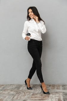 フォーマルな服装で歩くと灰色の背景に分離されたテイクアウトのコーヒーを手に携帯電話で話しているかなりビジネス女性の完全な長さの画像
