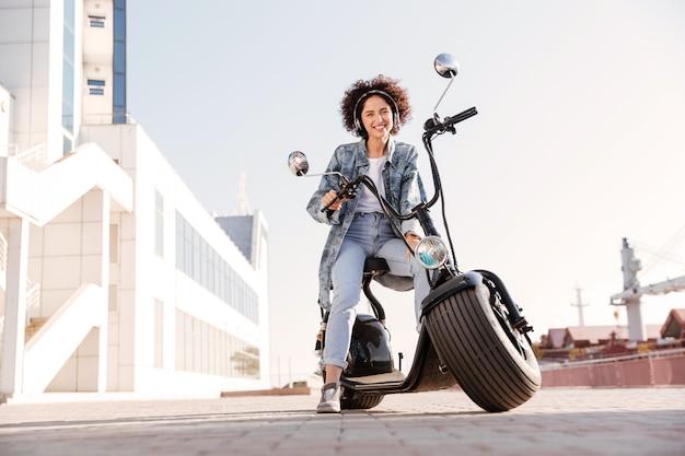 Полнометражное изображение улыбающейся кудрявой женщины, сидящей на мотоцикле