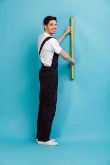 Полное изображение улыбающегося мужчины-строителя, держащего инструмент уровня на стене над синей стеной