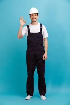 Полное изображение улыбающегося мужчины-строителя в защитном шлеме, показывающего знак ок на синей стене