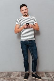 スマートフォンを持って笑顔の男の全身画像
