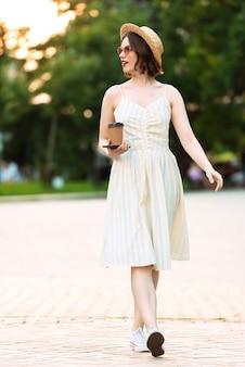 Полное изображение улыбающейся женщины в платье, соломенной шляпе и солнцезащитных очках, идущей с чашкой кофе на открытом воздухе