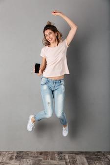 Полнометражное изображение улыбающейся женщины в футболке, слушающей музыку со смартфона с наушниками во время прыжков и на сером
