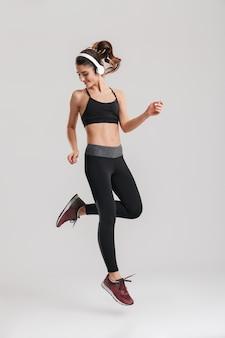 灰色の壁に分離されたワイヤレスヘッドフォンでジャンプするスポーツウェアのインストラクターの強い意志のある女性フィットネストレーナーの全身像