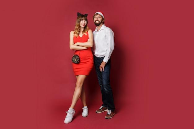 Полнометражное изображение стильной пары в влюбленности в шлемах маскарада нового года стоя на красном цвете.