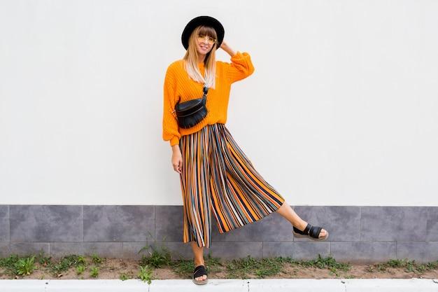 Полнометражное изображение стильной женщины, стоящей на белом в стильном оранжевом свитере и многоцветной полоске-юбке