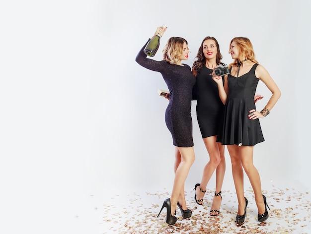 クレイジーなパーティーで時間を過ごし、ダンスをし、楽しんで、笑っている3人の幸せな女の子の全身像。エレガントなカジュアルなドレスを着て、かかと、明るいメイク。シャンパンを飲みます。テキストのためのスペース。