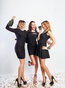 クレイジーなパーティーで時間を過ごし、踊り、楽しんで、笑っている3人の幸せな女の子の完全な長さの画像。エレガントなカジュアルドレス、かかと、明るいメイクを着ています。シャンパンを飲む。テキスト用のスペース。