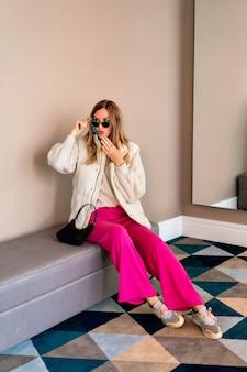 Полнометражное изображение модной блондинки, позирующей в роскошном отеле, в теплой красочной повседневной одежде