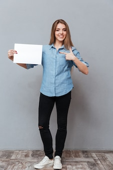 空白のボードを示すシャツの女性の完全な長さの画像