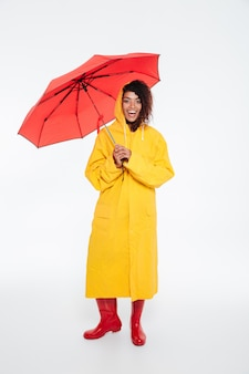 Full length image of pleased african woman in raincoat