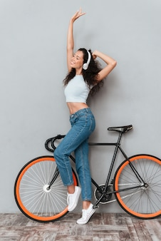 Full length image of pleased curly woman standing with bicycle and listening music by the headphone with closed eyes over gray background