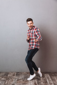 Full length image of pleased man in shirt and jeans pointing and looking