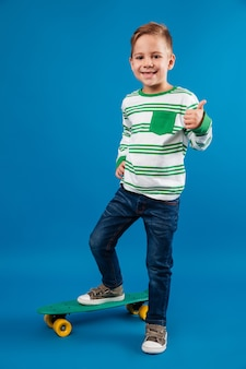 Full length image of pleased young boy posing with skateboard